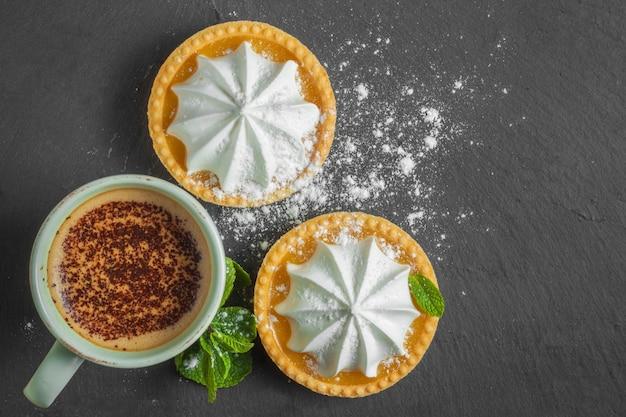 Crostata al limone con foglie di menta e una tazza di cappuccino con topping al cioccolato