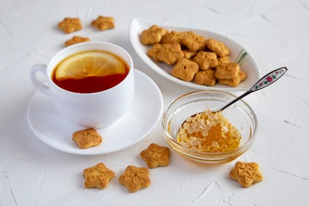 Tè al limone, favo di miele e biscotti su un tavolo bianco
