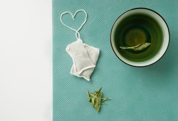 Tè al limone verbena in tazza e bustine di tè con cordino a forma di cuore. vista dall'alto. lay piatto