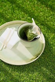Tè alla verbena al limone in una tazza con bustina di tè fatta a mano su erba verde. concetto di intimità. avvicinamento. luce naturale.