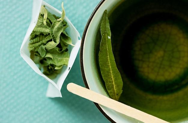 Tè alla verbena di limone in una tazza con una bustina di tè fatta a mano aperta. vista dall'alto. lay piatto