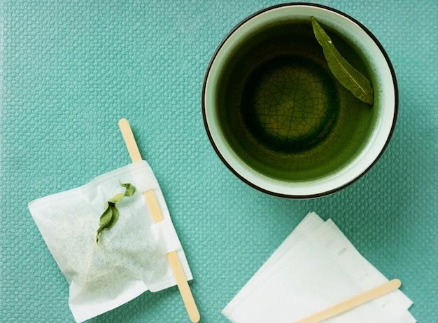 Tè lemon verbena in una tazza con bustina di tè fatta a mano su una scrivania verde acqua di mare. vista dall'alto. lay piatto