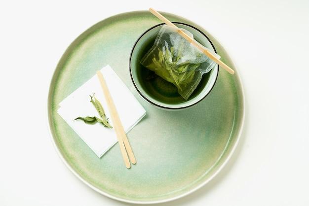 Tè al limone verbena in tazza con bustina di tè fatta a mano. vista dall'alto. lay piatto.
