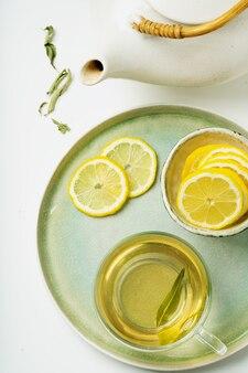 Tè al limone verbena servito con limone, decorato con foglie secche di verbena con teiera vintage. lay piatto. vista dall'alto
