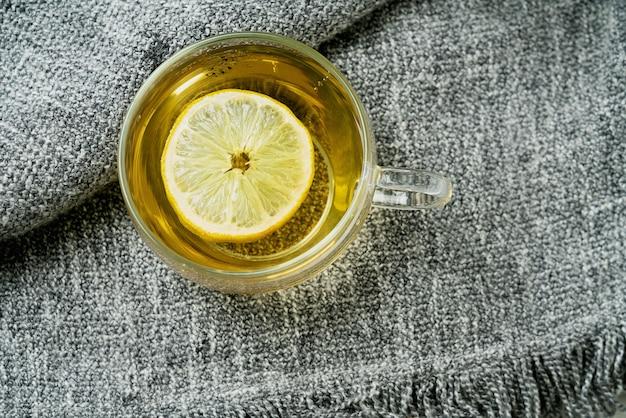 Tè lemon verbena servito con limone su una coperta grigia. lay piatto. vista dall'alto