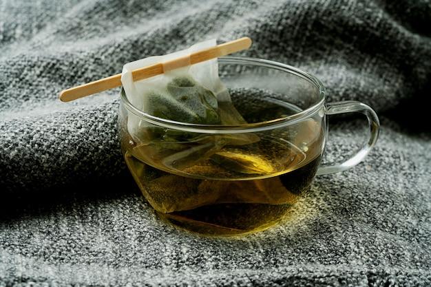 Tè alla verbena al limone con bustina di tè fatta a mano su una coperta grigia. avvicinamento