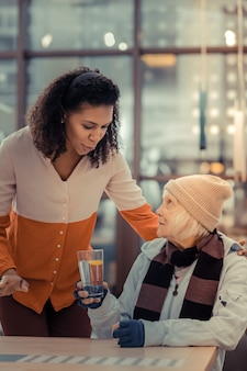 Limonata. piacevole donna anziana con in mano un bicchiere d'acqua mentre parla con una gentile giovane donna