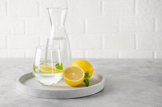 Acqua di limone con limoni freschi e foglie di menta su uno sfondo grigio cemento.
