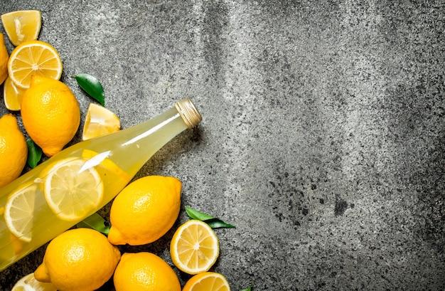Limonata in bottiglia con fettine di limoni freschi.