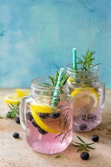 Limonata o cocktail con mirtilli, limone e rosmarino, bevanda rinfrescante fredda con ghiaccio sul tavolo
