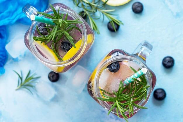 Limonata o cocktail con mirtilli e rosmarino bevanda rinfrescante fredda con ghiaccio