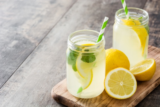 Bevanda della limonata in un vetro del barattolo su copyspace di legno