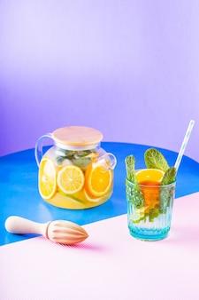 Bevanda di limonata di acqua, limone, arancia e foglie di menta su sfondo multicolore