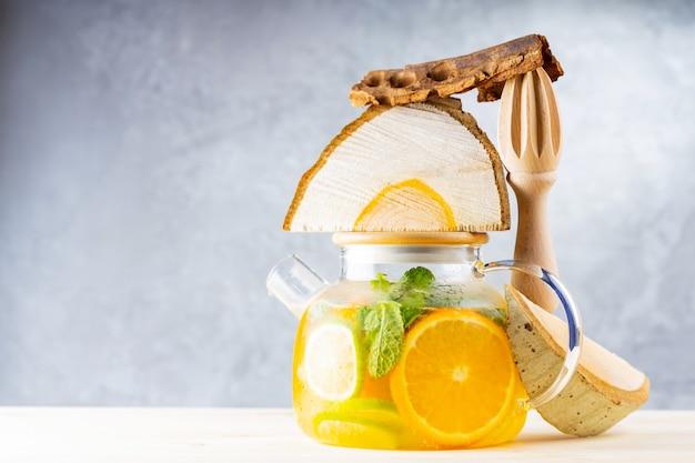 Limonata a base di acqua, limone, arancia e foglie di menta in una teiera trasparente. tè freddo alla menta lime e pezzi di legno. composizione creativa