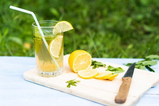 Limonata in un bicchiere e limoni a fette con menta