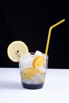 Limonata in un bicchiere con una cannuccia su un tavolo bianco e uno sfondo nero. minimalista