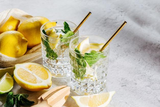 Limonata su bicchieri e limoni e lime sulla borsa del mercato bianco su sfondo marmo