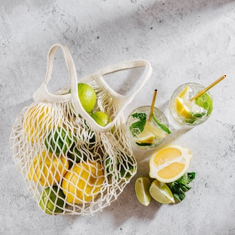 Limonata su bicchieri e limoni e lime su borsa da mercato a rete bianca su sfondo marmo