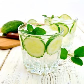 Limonata con cetriolo e menta in due bicchieri, un coltello, un cetriolo sulle tavole di legno chiaro di sfondo