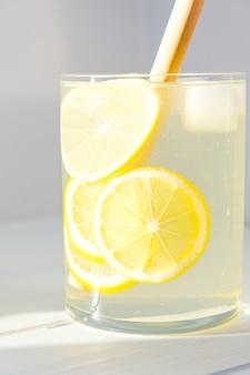 Limonata con limone e ghiaccio in un bicchiere.