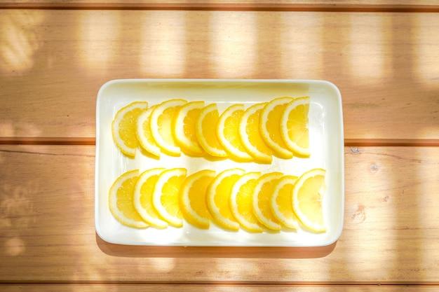 I limoni o le limette sono utilizzati come ingrediente per cucinare e bere. è disposto sul quadrato bianco della ciotola del rettangolo sul piatto di legno del tavolo in giardino con la luce del sole.