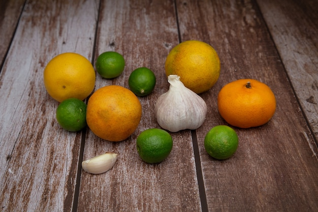 Limoni, arance, aglio e mandarini su fondo in legno