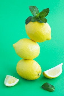 Limoni impilati piramide sullo sfondo verde. posizione verticale.