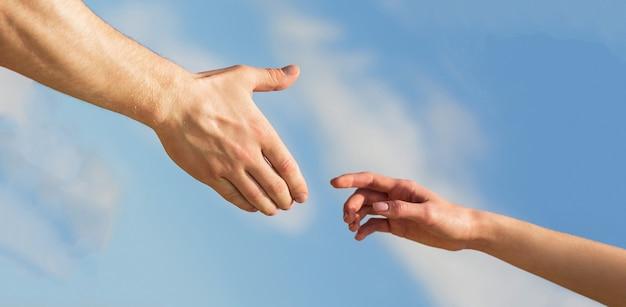 Dare una mano. solidarietà, compassione e carità, soccorso. le mani dell'uomo e della donna che si raggiungono l'un l'altra, si sostengono. dare una mano. mani dell'uomo e della donna sul fondo del cielo blu.