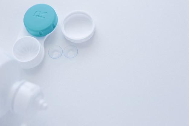 Un contenitore per lenti, un liquido per la conservazione delle lenti e due lenti a contatto si trovano sul lato su uno sfondo bianco ...