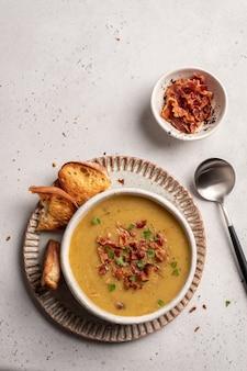 Zuppa di piselli di lenticchie guarnire con pancetta e costine di maiale