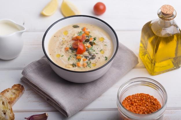 Purea di zuppa di lenticchie con pomodori, cetrioli e noci in una ciotola Foto Premium