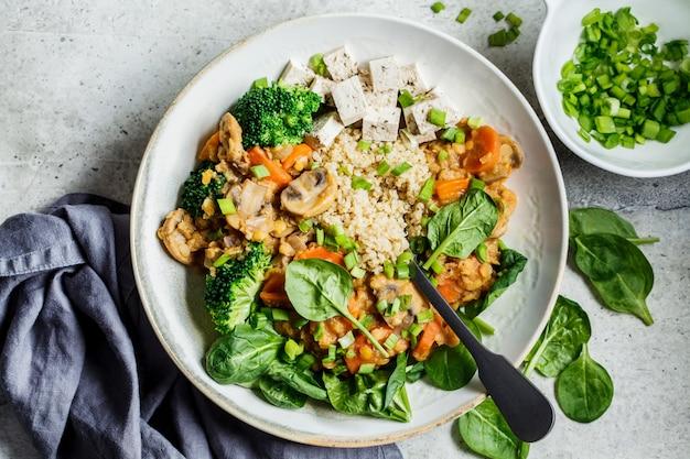 Stufato vegano di lenticchie con funghi, quinoa, spinaci e broccoli in una ciotola, vista dall'alto. concetto di cibo sano vegan.