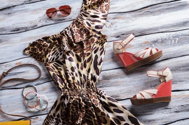 Abito leopardato e bracciali luminosi. sandali con zeppa con abito di lusso. nuovi articoli alla boutique di moda. abbigliamento esclusivo in vendita.