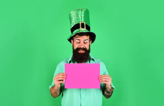 Leprechaun in cappello verde tiene cartellone pubblicitario rosa festa di san patrizio cappello verde saint