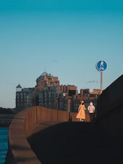 Coppia lesbica da dietro cammina attraverso un ponte, con il paesaggio della città