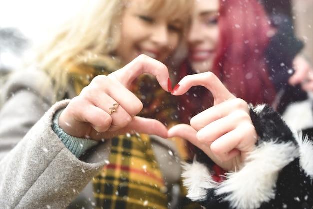Coppia lesbica che fa il cuore con le mani, relazione aperta nell'amore di samesex. migliori amiche. concetto di amicizia.