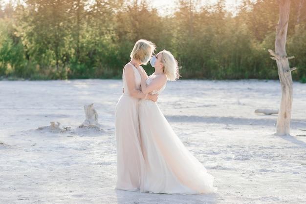 Coppia lesbica matrimonio sulla sabbia che indossa maschere