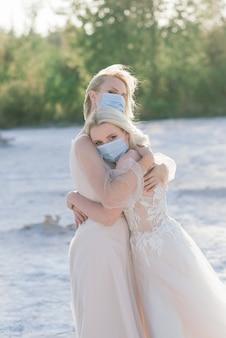 Matrimonio di coppia lesbica sulla sabbia bianca, indossa maschere per prevenire l'epidemia di covid-19