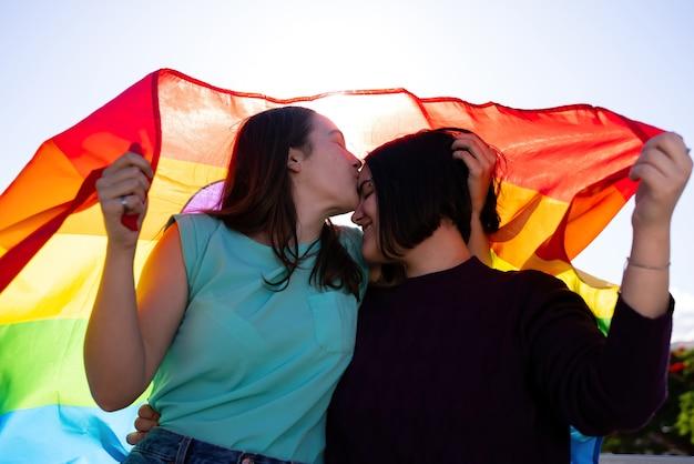 Ragazze lesbiche che si divertono a dipingersi e con la bandiera lgtb il giorno dell'orgoglio lgtb concept