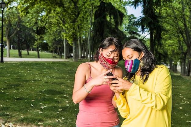 Coppia lesbica latina lesbica che sms con tecnologia smartphone e maschera facciale durante la pandemia di covid19 giovane giallo e lavanda lgtbq