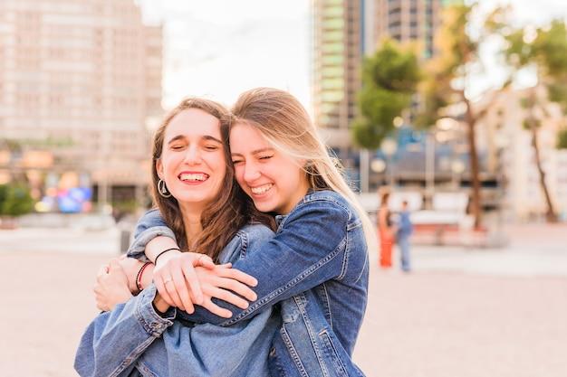Lesbiche giovani coppie multietniche si abbracciano su un'alba solare insieme amiche di felicità
