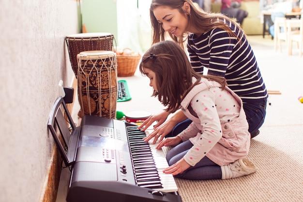 Lezione di suonare il pianoforte. la giovane insegnante insegna a una bambina a suonare il sintetizzatore