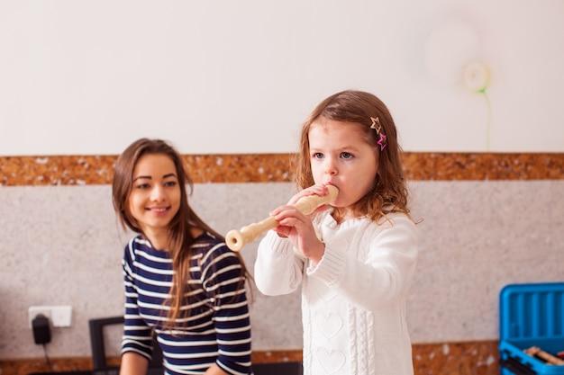 Lezione di suonare la pipa. la giovane insegnante insegna a una bambina a suonare il flauto