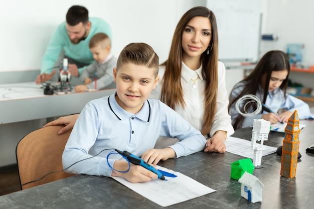 Lezione nella sala robotica. mamma e figlio usano una penna per la stampa 3d.