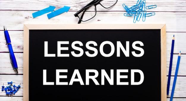 Lezioni imparate scritte su una lavagna nera accanto a graffette blu, matite e una penna.