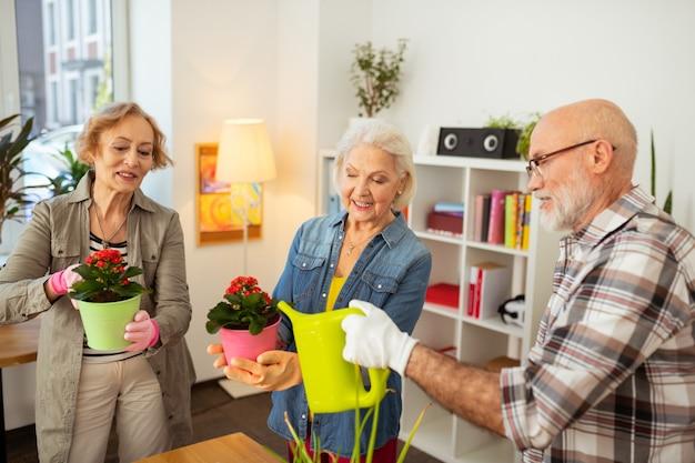 Lasciami aiutare. simpatico uomo anziano che guarda i suoi amici mentre si offre di innaffiare i fiori