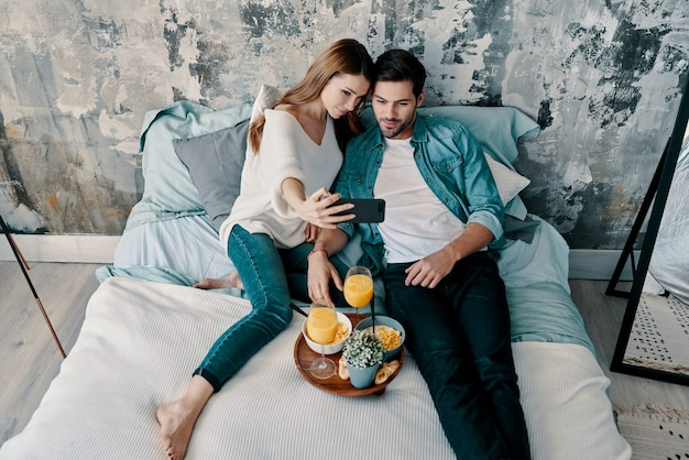 Fammi fare un selfie! vista dall'alto di una bella giovane coppia che si fa selfie e sorride mentre trascorre il tempo a letto a casa