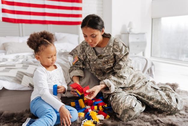 Fammi provare anche io. tenera donna splendida amorevole che gioca con il suo bambino costruendo qualcosa utilizzando uno speciale set di costruzioni colorate