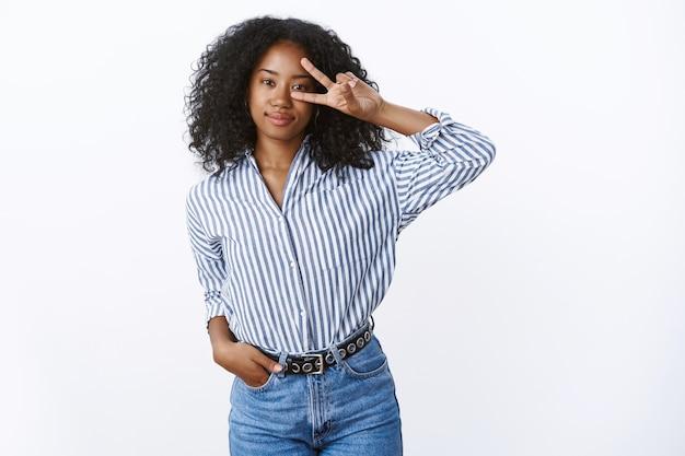 Lascia che il rock party. ritratto fiducioso di bell'aspetto elegante donna afroamericana taglio di capelli riccio tenere i jeans della tasca della mano che mostrano la vittoria in discoteca gesto di pace sull'occhio sorridente sicuro di sé, pronto rock-n-roll