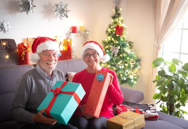 Festeggiamo il natale insieme. una bella coppia di anziani che si gode lo scambio di doni. indossano i cappelli di babbo natale. bellissimo albero di natale sullo sfondo e regali per la famiglia